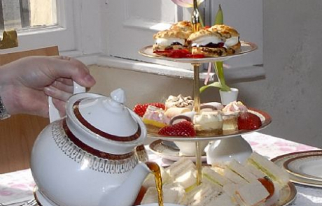A selection of sandwich's and cake on a platter, Someone pouring tea from a teapot at the Priory House Tea Rooms